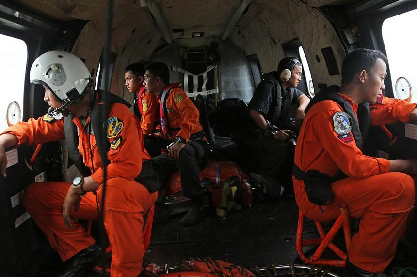 Crew members of an Indonesian Air Force NAS 332 Super Puma helicopter look out of the windows during a search operation for the victims and wreckage of AirAsia flight QZ8501 over the Java Sea, Indonesia, on Jan 5, 2015. -- PHOTO: AFP