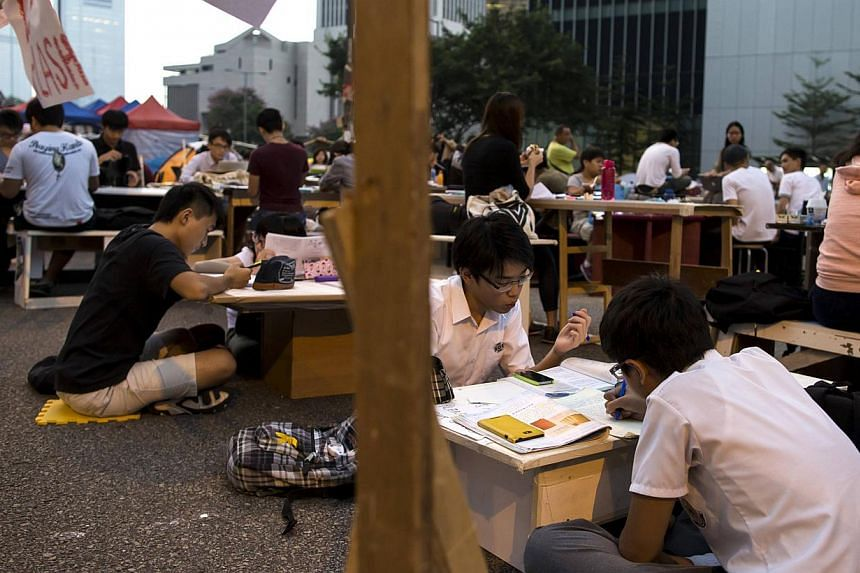 Occupy Central protesters sit at a study area along the main street to the financial Central district as they continue blocking areas outside of the government headquarters building in Hong Kong on Oct 20, 2014. -- PHOTO: REUTERS