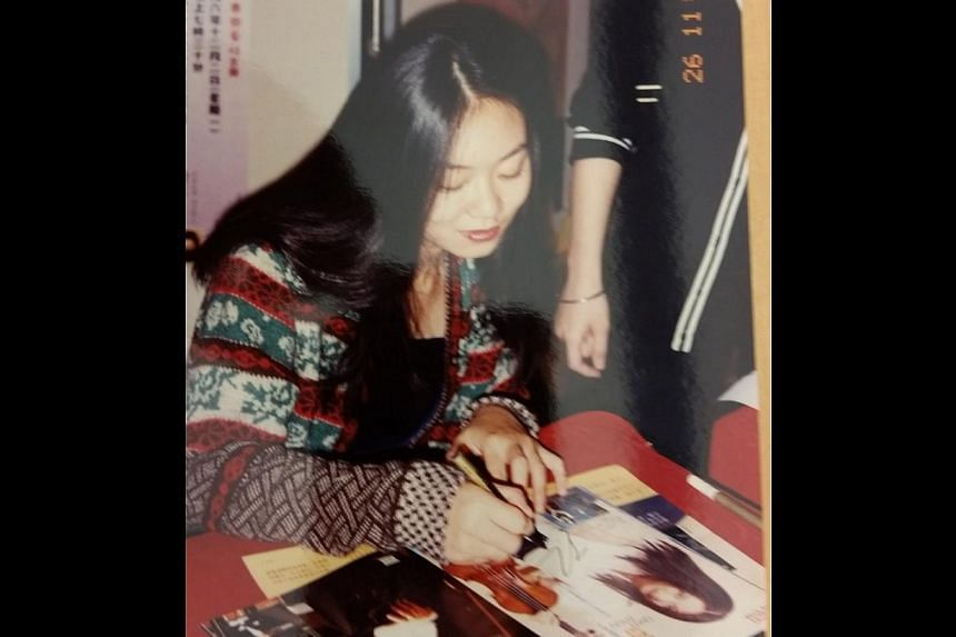 Qian Zhou at age 18, after winning the 1987 Marguerite Long-Jacques Thibaud Competition in Paris; and in 1996 (above), signing photographs after a concert. -- PHOTO: COURTESY OF QIAN ZHOU