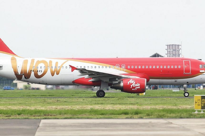 An AirAsia plane in Surabaya on Jan 3, 2015. Indonesia's transport ministry has ordered airport authorities to take action against staff who allowed Indonesia AirAsia to fly outside its approved schedule. -- PHOTO: SPH