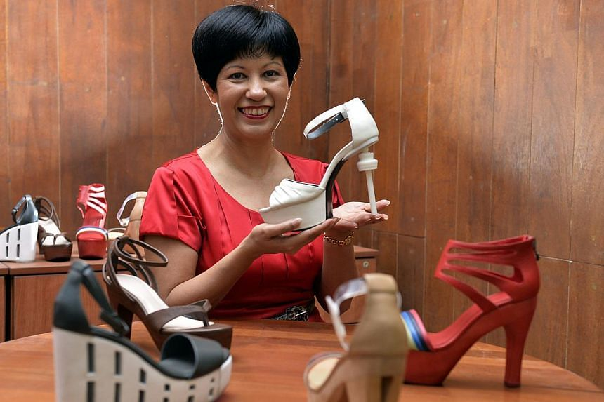 Ms Indranee Rajah holding a pair of shows inspired by the Changi Control Tower. -- ST PHOTO: DESMOND FOO