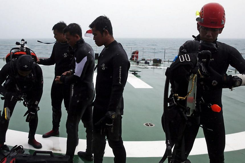 A group of divers preparing their gear on the deck of the ship KN Purworejo during a search operation for passengers onboard AirAsia Flight QZ8501 in the Java Sea on Jan 4, 2015. -- PHOTO: REUTERS