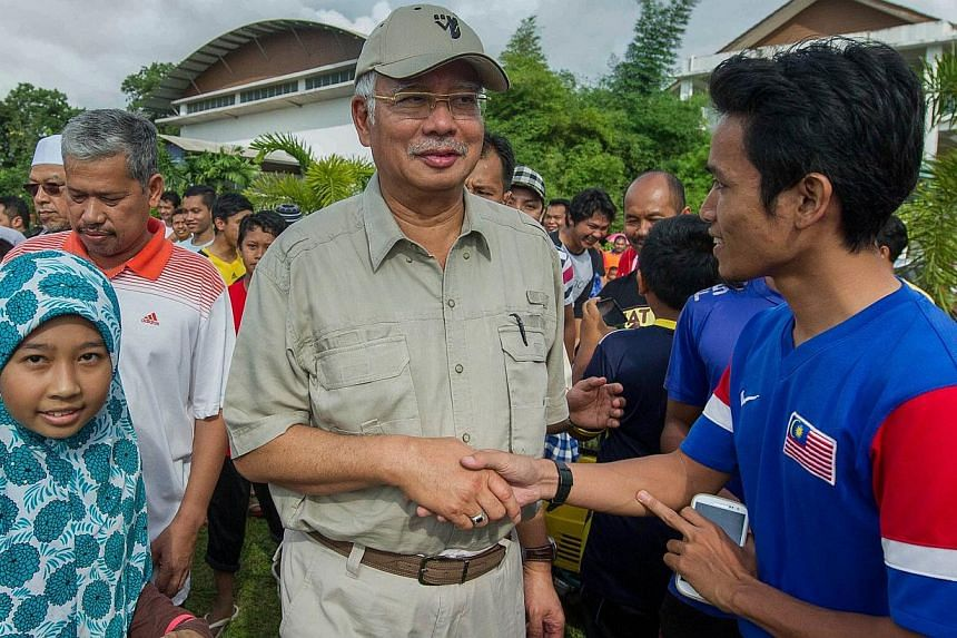 Flood victims greeting Malaysian Prime Minister Najib Razak (centre) as he arrives at an evacuation center in Pasir Mas, on the outskirts of Kota Bharu, on Dec 27, 2014. -- PHOTO: AFP