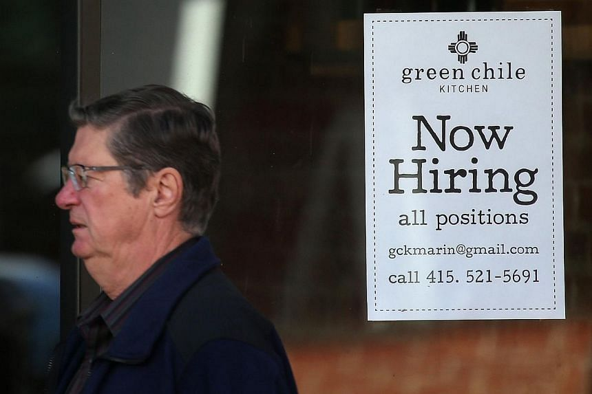 """A pedestrian walks past a """"now hiring"""" sign posted on the window of a shop on Nov 7, 2014 in San Rafael, California. Last year, the U.S. economy recovered all of the jobs lost during the Great Recession and more. -- PHOTO: AFP"""