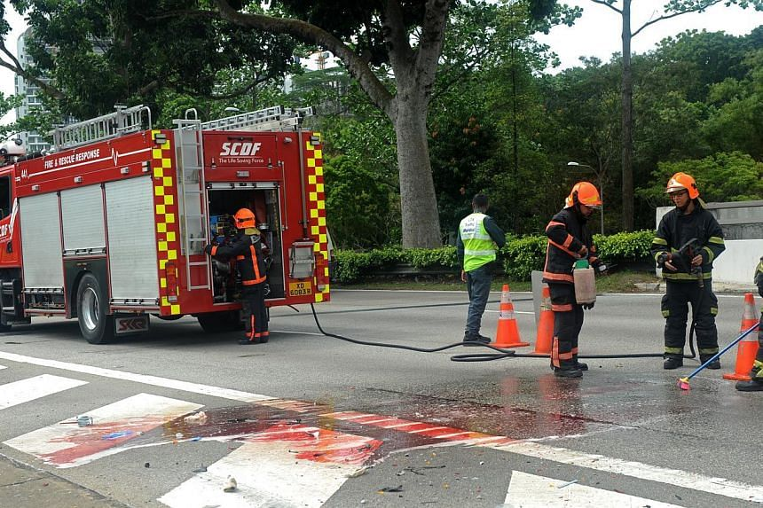 SCDF washing the blood off the road. -- ST PHOTO: TIFFANY GOH