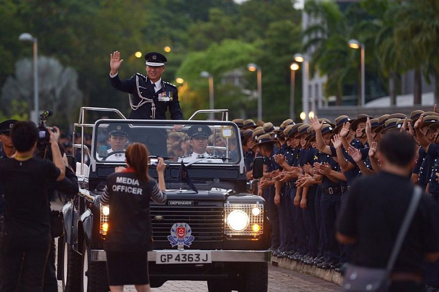 Outgoing Police Commissioner Ng Joo Hee waving to members of the police force during his farewell ceremony.-- ST PHOTO:DESMOND WEE