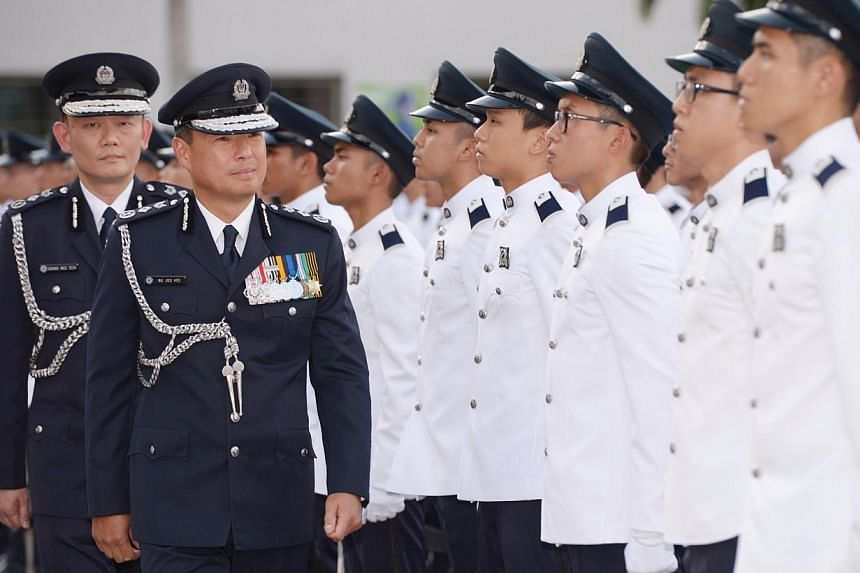 Outgoing police commissioner Ng Joo Hee (right) inspecting the Guard of Honour during his farewell ceremony with incoming Police Commissioner Hoong Wee Teck (left).-- ST PHOTO:DESMOND WEE