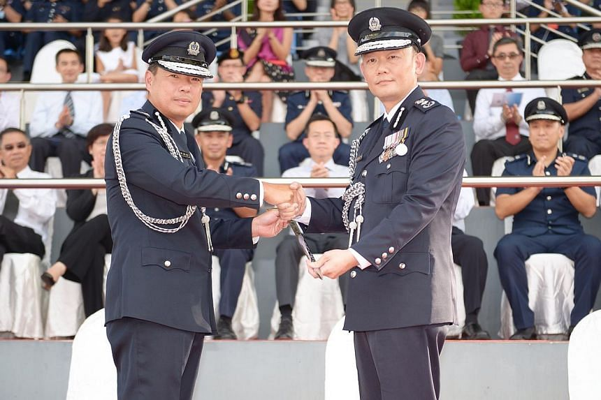 Mr Ng Joo Hee (left), who has been the police commissioner for the past five years, handing over command of the Singapore Police Force to incoming Police Commissioner Hoong Wee Teck.-- ST PHOTO:DESMOND WEE