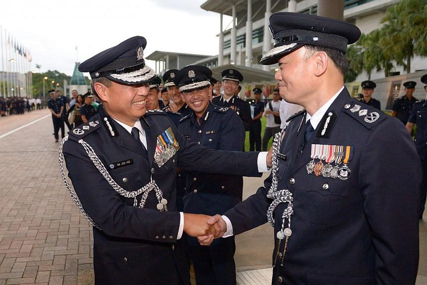 Mr Ng Joo Hee (left) who has been leading the Singapore Police Force (SPF) for close to five years, greeting incoming Police Commissioner Hoong Wee Teck (right). -- ST PHOTO:DESMOND WEE