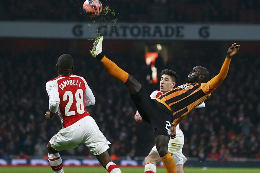 Yannick Sagbo of Hull City stretches for the ball during their FA Cup third round soccer match against Arsenal at the Emirates Stadium in London on Sunday. -- PHOTO: REUTERS