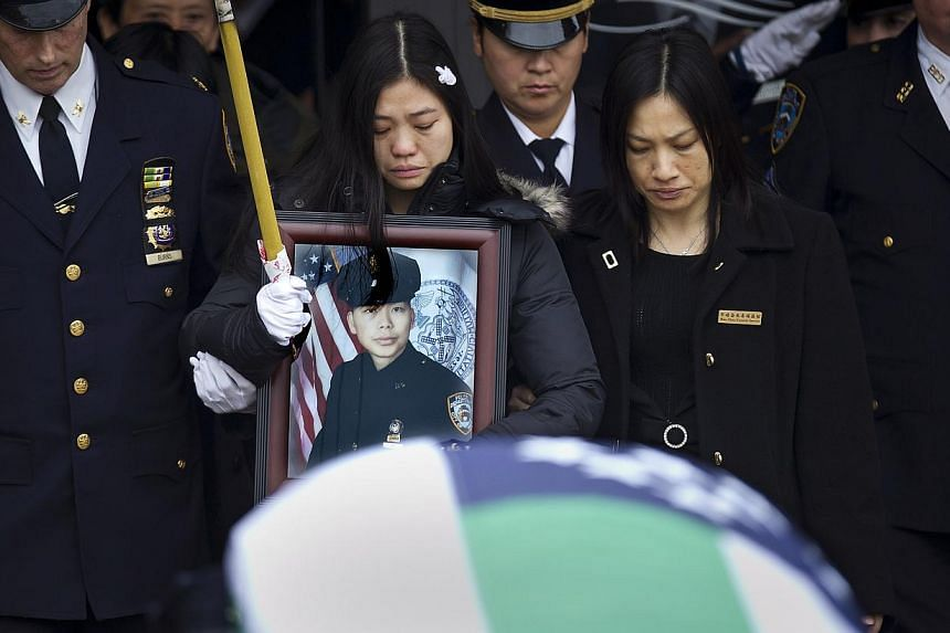 Widow Chen Pei Xia holds a photo of her husband, slain New York Police Department officer Liu Wenjian, as his casket departs his funeral in the Brooklyn borough of New York on Sunday. New York Mayor Bill de Blasio appealed for reconciliation on Sunda
