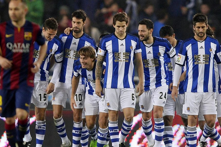 Real Sociedad's players celebrate Barcelona's own goal during their Spanish first division match at Anoeta stadium in San Sebastian on Jan 4, 2015. -- PHOTO: REUTERS