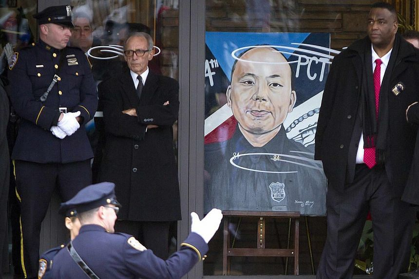 Police officers stand outside during the funeral for slain New York Police Department officer Liu Wenjian in the Brooklyn borough of New York on Jan 4, 2015. -- PHOTO: AFP