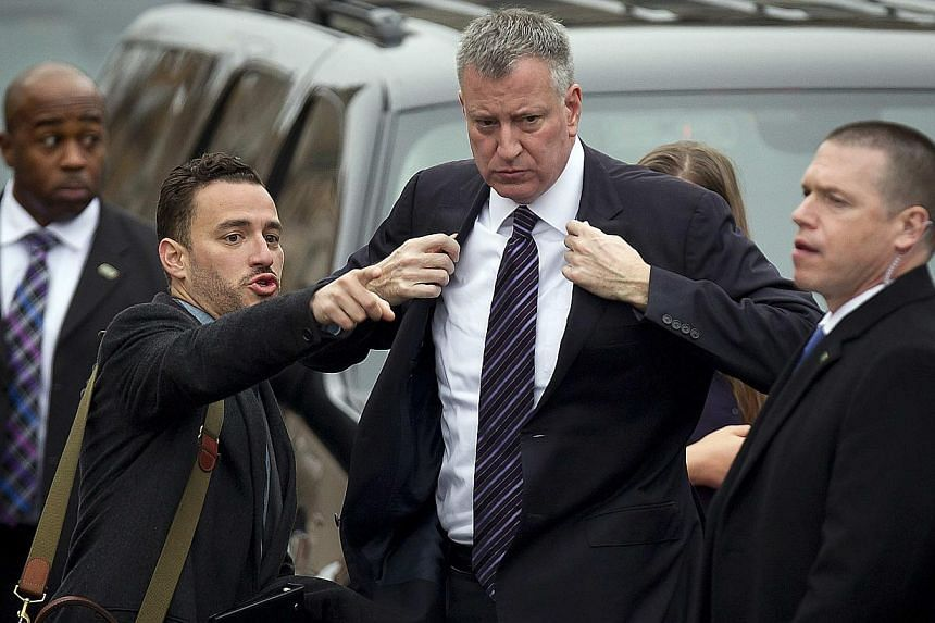 New York City Mayor Bill de Blasio (2nd right) arrives with his Director of Advance Frankie Martinez Blanco (2nd left) for the funeral of slain New York Police Department officer Liu Wenjian in the Brooklyn borough of New York on Jan 4, 2015. --