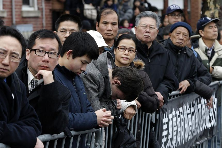 Mourners stand together on the sidewalk as they listen to the funeral service for New York Police Department officer Liu Wenjian in the Brooklyn borough of New York on Jan 4, 2015. -- PHOTO: REUTERS