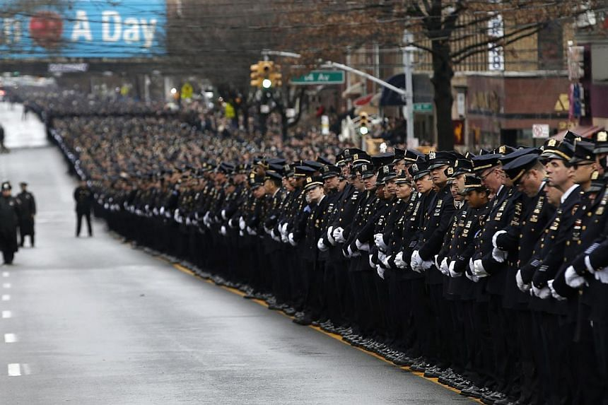 Police stand in formation down 65th street as they listen to the funeral service for New York Police Department officer Liu Wenjian in the Brooklyn borough of New York on Jan 4, 2015. -- PHOTO: AFP