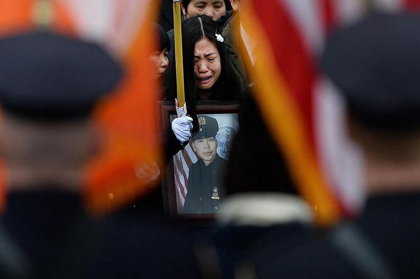 Pei Xia Chen (centre), the widow of slain New York Police Department (NYPD) officer Wenjian Liu, cries while holding a picture of her husband during his funeral in New York's borough of Brooklyn on Jan 4, 2015. -- PHOTO: AFP