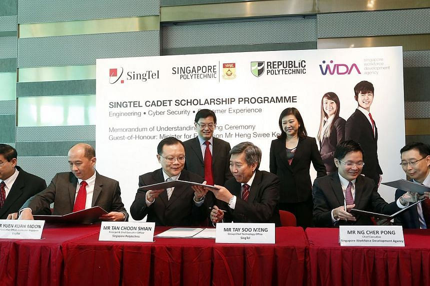 Minister for Education Heng Swee Keat (back row, left) witnesses the signing of an MOU for a new diploma scholarship programme launched by telco SingTel on Tuesday, and jointly developed with Singapore and Republic polytechnics.  -- ST PHOTO: CH