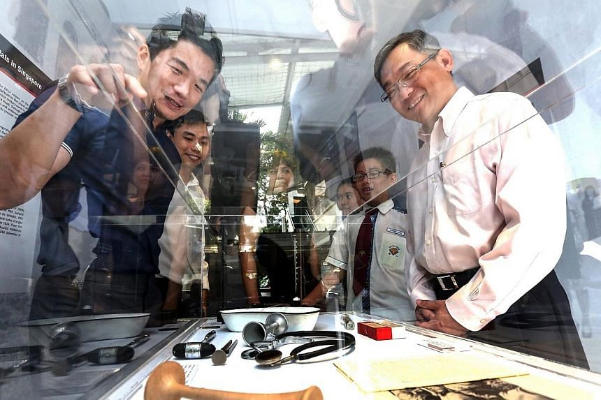Health Minister Gan Kim Yong looking at the artefacts on display in the mobile truck exhibition at South View Primary School on Jan 5, 2014. -- PHOTO: LIANHE ZAOBAO