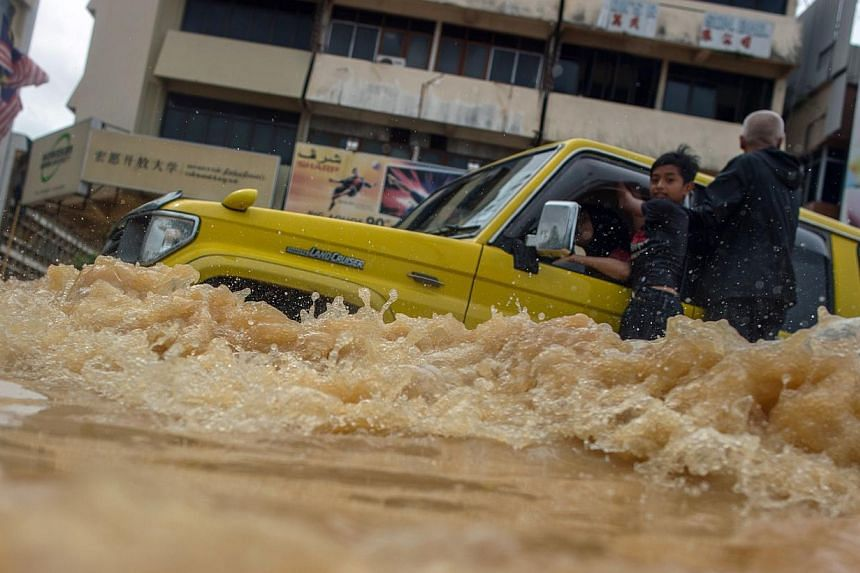 A vehicle ploughing through flood waters in Kota Baru last month. Natural disasters are likely to feature again as global warming gets worse. The new year will also bring economic challenges for Malaysia as the US economy recovers and investors pull