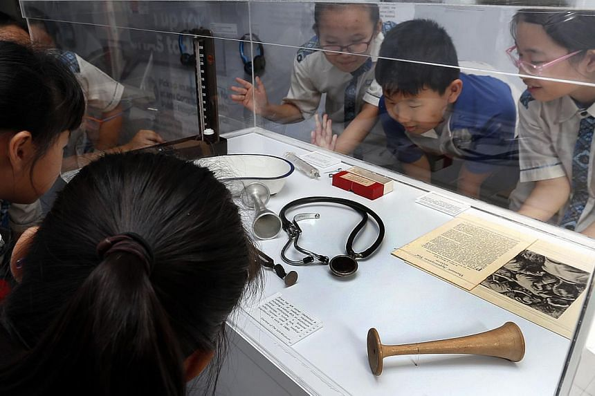 South View Primary School pupils looking at artefacts on display at the exhibition, including a wooden monoaural stethoscope (bottom right) used by Western medical doctors in 1911. The exhibition was launched at their school yesterday, and is housed
