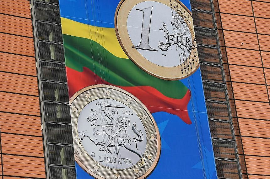A detail of a banner welcoming Lithuania into the Eurozone hung on the European Commission headquarters in Brussels on Jan 5, 2015. The euro wallowed near a nine-year trough early on Tuesday as the prospect of more policy easing from the European Cen
