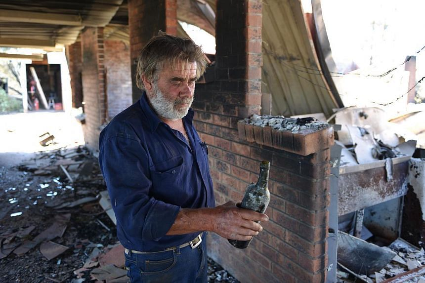 Resident David Miller carrying a wine bottle that melted in the intensity of the heat when his home near Kersbrook was destroyed by a bushfire in the Adelaide Hills on Jan 5, 2015. -- PHOTO: AFP