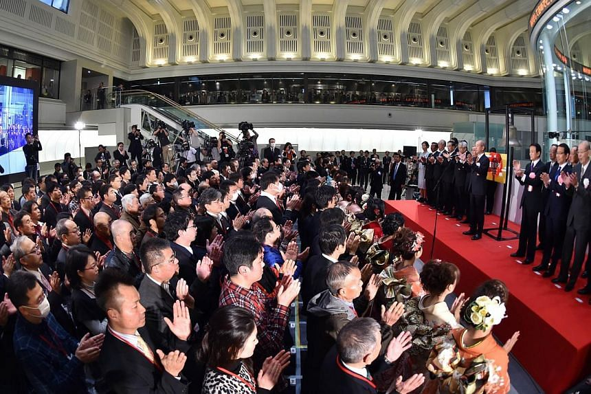 Executives of the Japan Exchange Group and visitors celebrating the first trading day of the year during the opening ceremony at the Tokyo Stock Exchange on Jan 5, 2015. Tokyo stocks opened 1.76 per cent lower on Tuesday following a slump in US share
