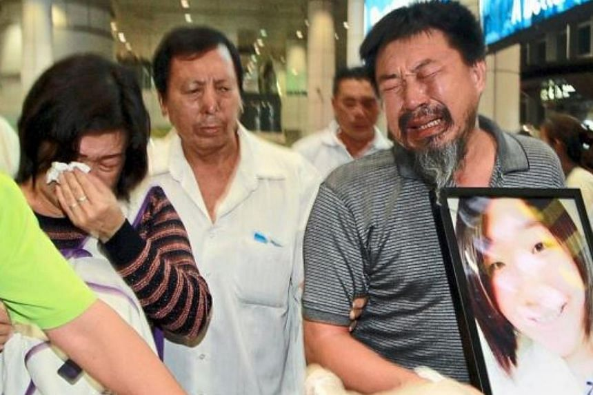The deceased's father, Tan Chin Hin, hugging a portrait of his only daughter while exiting the arrival hall, followed by his sobbing wife, Ms Lee Siew Yan,and two sons on Monday. -- PHOTO: THE STAR / ASIA NEWS NETWORK