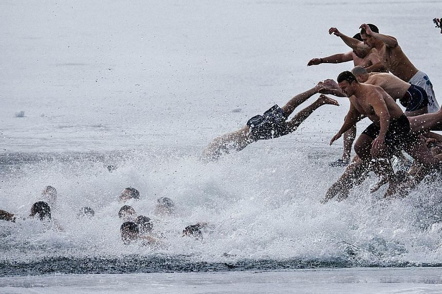 Bulgarians dive into the icy waters of a lake to catch a cross in Sofia as part of Epiphany Day celebrations on Tuesday. It is believed that the first man to grab the cross, thrown into the water by an Eastern Orthodox priest, will be healthy through