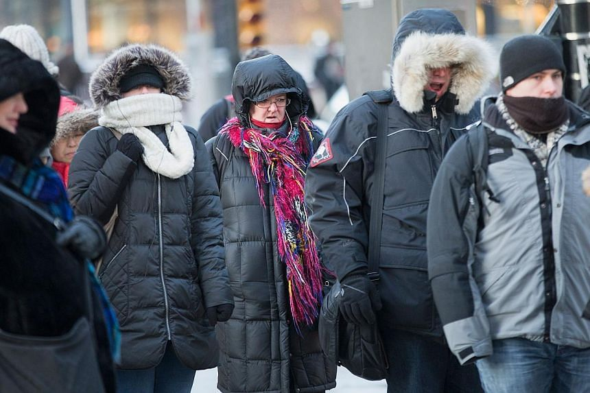 Commuters make their way to work as temperatures hovered around -20 degrees C during the morning rush on Monday in Chicago, Illinois. Temperatures are expected to remain well below zero today and the rest of the week with snow squalls. -- PHOTO: AFP