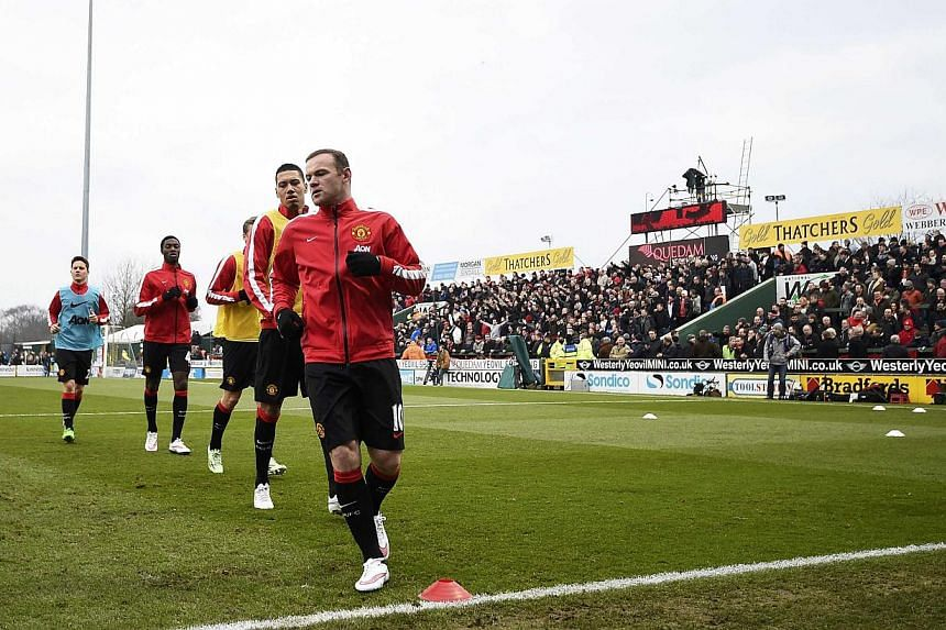 Manchester United players warm up ahead of their FA Cup third round soccer match on Sunday. -- PHOTO: REUTERS