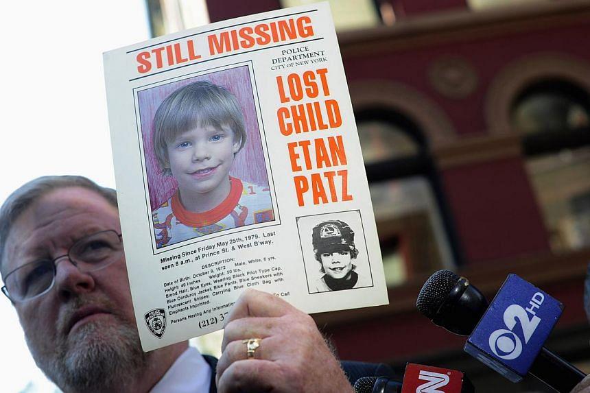 New York Police Department spokesman Paul Brown holding an original missing poster of Etan Patz during a news conference near a New York City apartment building, where police and FBI agents were searching a basement for clues in the boy's 1979 disapp