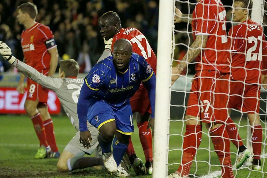 AFC Wimbledon's Adebayo Akinfenwa (centre) celebrates after scoring during the FA Cup third round soccer match against Liverpool at Kingsmeadow Stadium in Kingston-upon-Thames, southern England on Jan 5, 2015. -- PHOTO: REUTERS