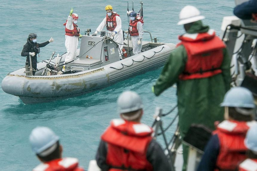 Recovery team from the the USS Sampson signalling the boat deck crew while conducting search and recovery operations in support of the Indonesian-led AirAsia flight QZ8501 search efforts in the Java Sea. An Indonesian official said on Wednesday that