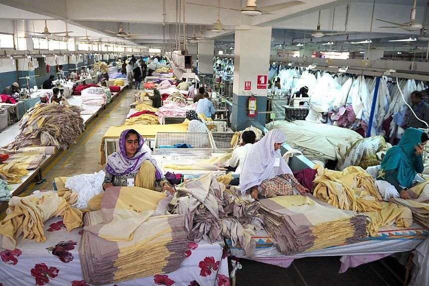 Pakistani employees working in a textile factory in Karachi on Nov 11, 2014,. More than two years after a fire tore through a Karachi clothing factory, killing 255 workers, no one has been prosecuted over the catastrophe. -- PHOTO: AFP