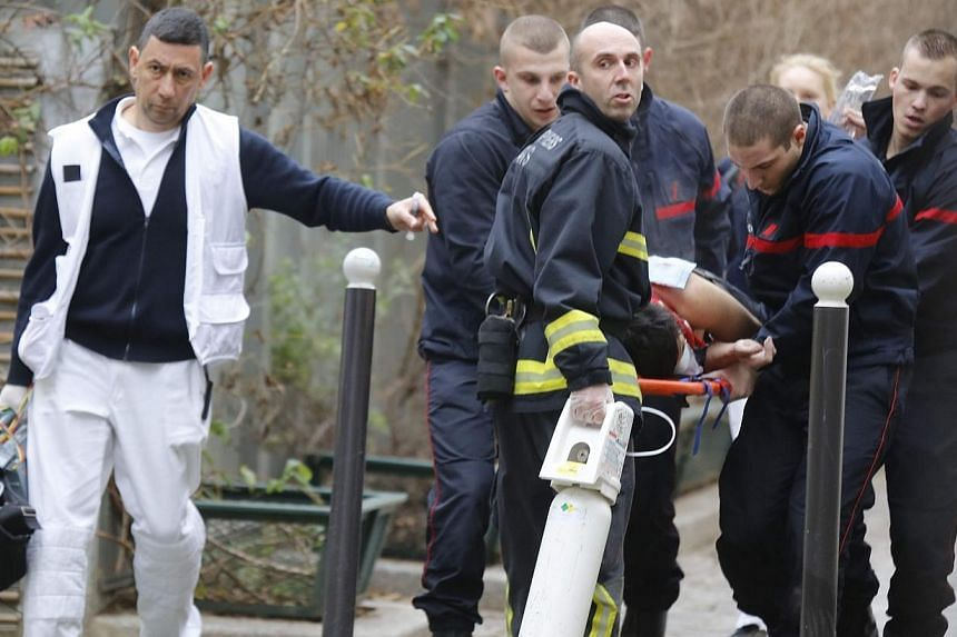 Firefighters carry a victim on a stretcher at the scene after a shooting at the Paris offices of Charlie Hebdo, a satirical newspaper, on Jan 7, 2015.The United States said it condemned Wednesday's deadly shooting attack on a French newspaper i