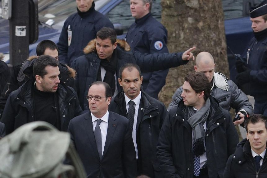 French President Francois Hollande (centre) arrives after a shooting at the Paris offices of Charlie Hebdo, a satirical newspaper, on Jan 7, 2015. -- PHOTO: REUTERS