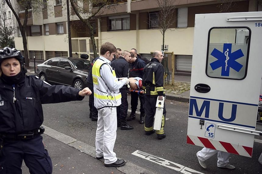 Firefighters carry an injured man on a stretcher in front of the offices of the French satirical newspaper Charlie Hebdo in Paris on Jan 7, 2015, after armed gunmen stormed the offices leaving at least 10 people dead. -- PHOTO: AFP