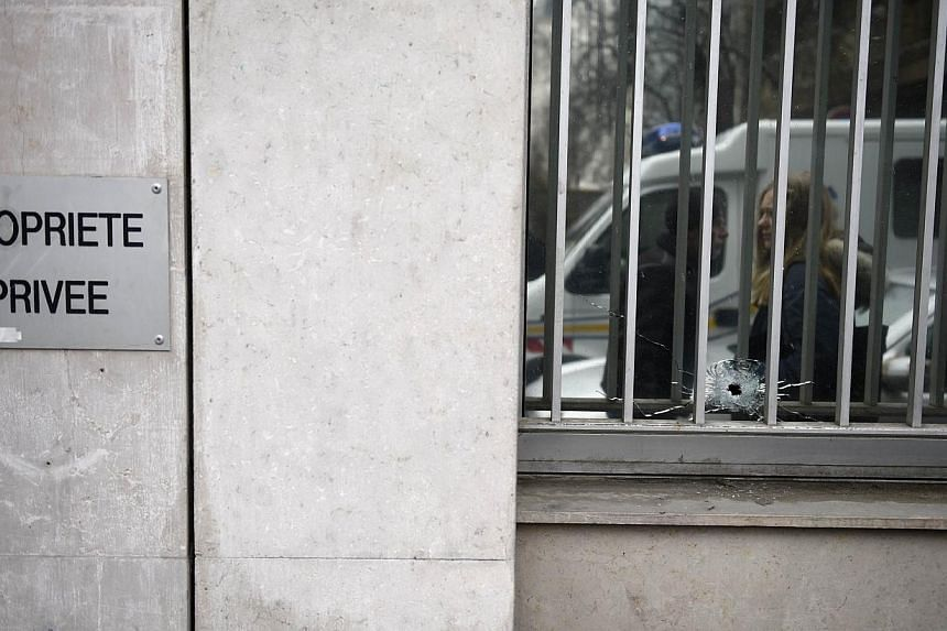 A window damaged by a bullet can be seen at the offices of the French satirical newspaper Charlie Hebdo in Paris on Jan 7, 2015, after armed gunmen stormed the offices leaving at least 10 people dead.-- PHOTO: AFP
