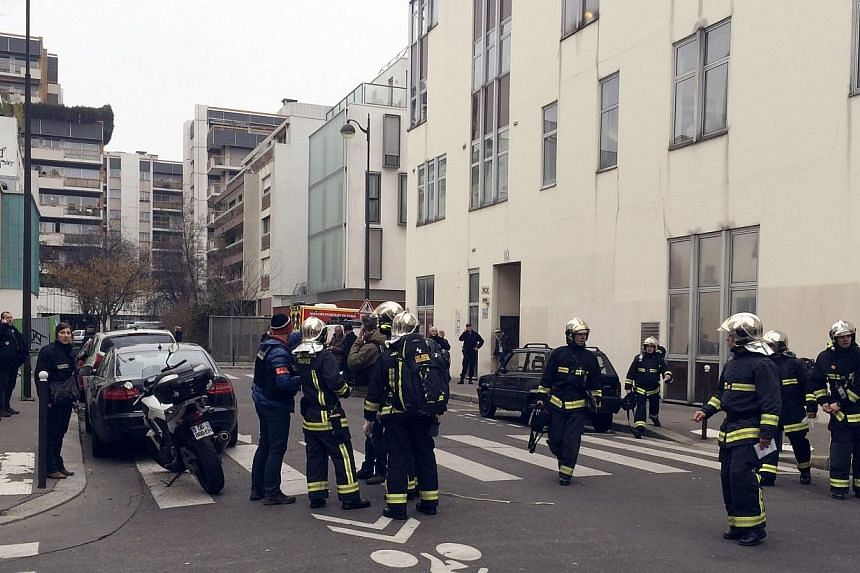 Police officers and firefighters gather in front of the offices of the French satirical newspaper Charlie Hebdo in Paris on Jan 7, 2015, after armed gunmen stormed the offices leaving at least 10 people dead. -- PHOTO: AFP