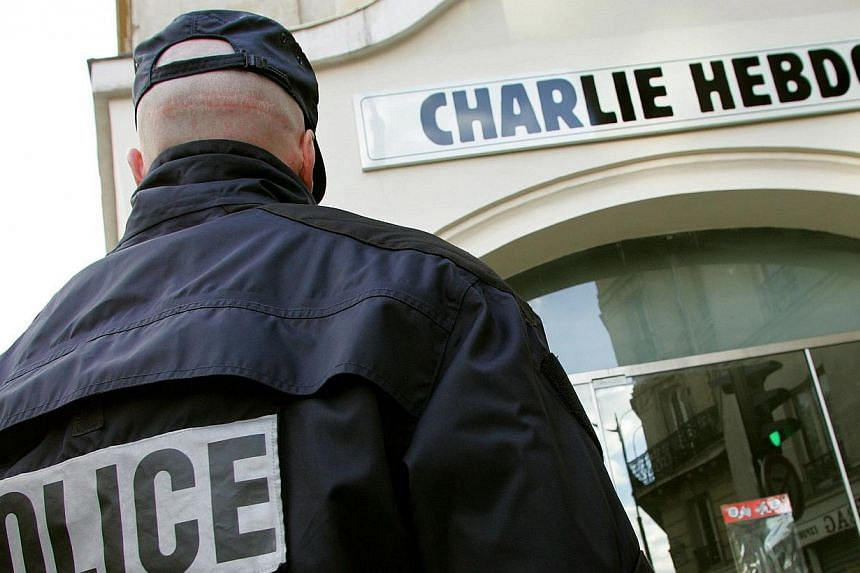 """A policeman stands guard outside the French satirical weekly """"Charlie Hebdo"""" in Paris in this Feb 9, 2006, file photo.The massacre on Wednesday at French weekly Charlie Hebdo took place after years of confrontation between the satirical publica"""