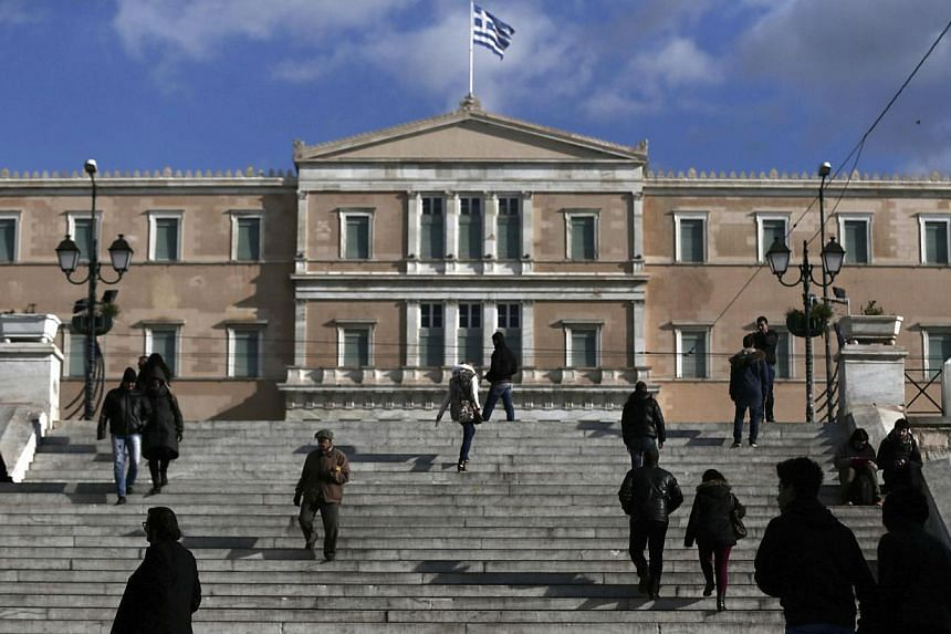 People making their way in central Syntagma Square with the parliament building in the background in Athens on Jan 6, 2015. Germany and France are taking a coordinated and calculated risk in the hope of averting a leftist victory in Greece's general