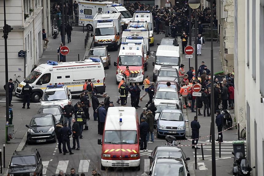 A general view shows firefighters, police officers and forensics gathered in front of the offices of the French satirical newspaper Charlie Hebdo in Paris on Jan 7, 2015, after armed gunmen stormed the offices leaving twelve dead. -- PHOTO: AFP