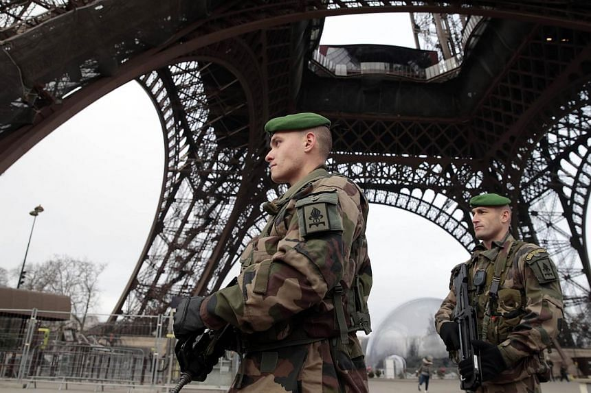 French soldiers patrol in front of the Eiffel Tower on Jan 7, 2015, in Paris as the capital was placed under the highest alert status after heavily armed gunmen shouting Islamist slogans stormed French satirical newspaper Charlie Hebdo and shot dead