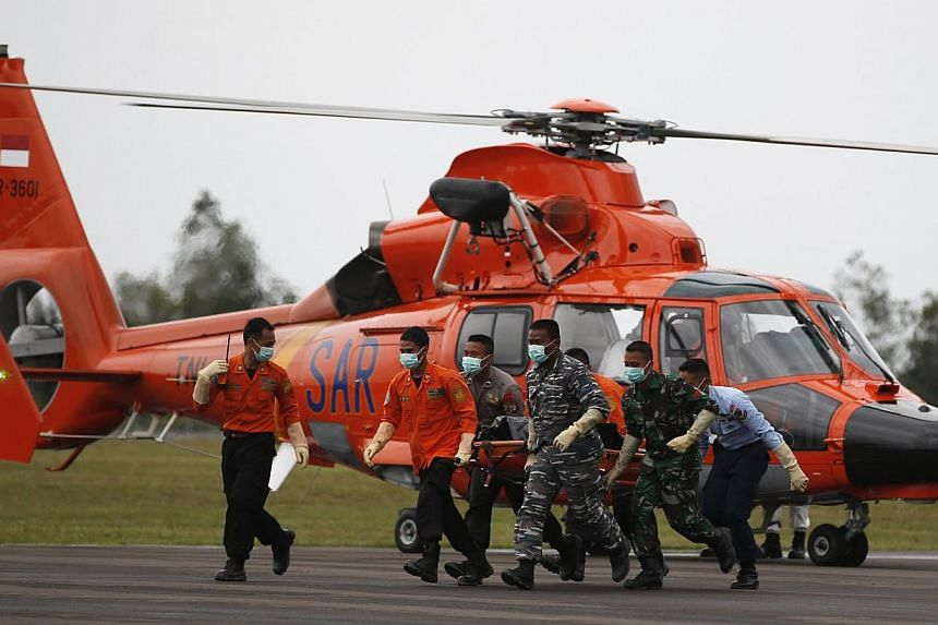 The body of an AirAsia QZ8501 passenger, recovered from the Java Sea, is carried to an ambulance after it arrived on a Indonesian Search and Rescue (BASARNAS) helicopter at an airbase in Pangkalan Bun, Central Kalimantan Jan 7, 2015. -- PHOTO: REUTER