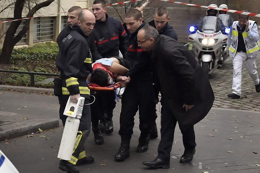 A victim is evacuated on a stretcher on Jan 7, 2015 after armed gunmen stormed the offices of the French satirical newspaper Charlie Hebdo in Paris, leaving at least 11 people dead. -- PHOTO: AFP