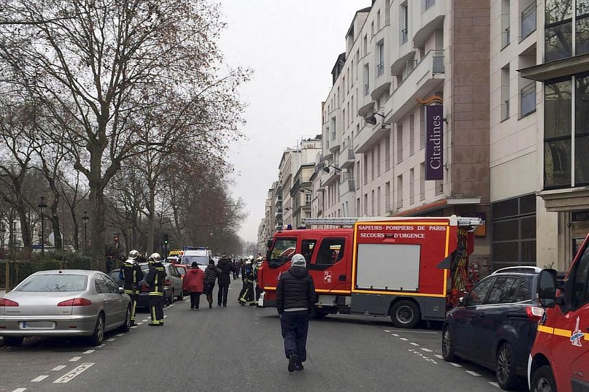 Firefighters and rescue services gather near the offices of the French satirical newspaper Charlie Hebdo in Paris on Jan 7, 2015, after armed gunmen stormed the offices leaving eleven dead, including two police officers, according to sources close to