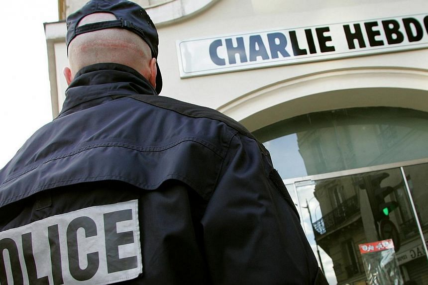"""A policeman stands guard outside the French satirical weekly """"Charlie Hebdo"""" in Paris in this Feb 9, 2006 file photo. At least 10 people were killed in a shooting at the Paris offices of Charlie Hebdo, a satirical newspaper firebombed in the past aft"""