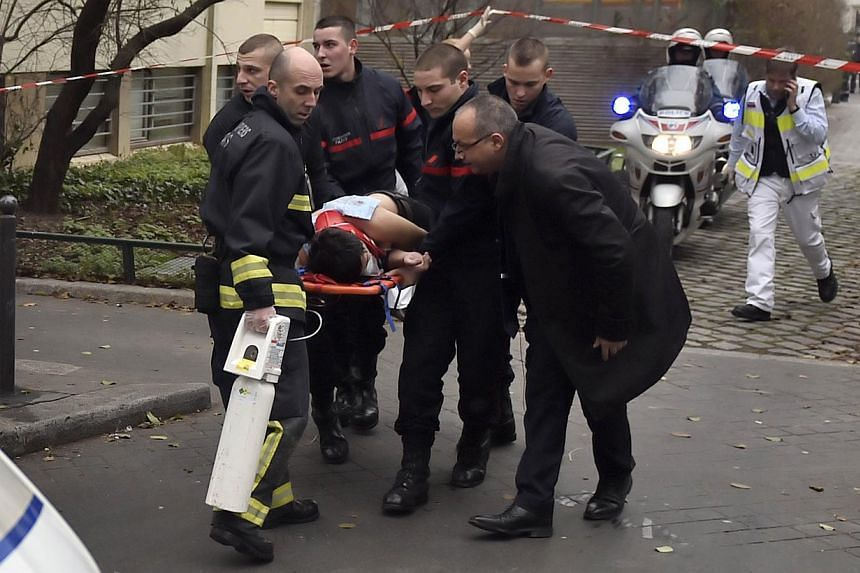 A victim is evacuated on a stretcher on Jan 7, 2015, after armed gunmen stormed the offices of the French satirical newspaper Charlie Hebdo in Paris, leaving at least 11 people dead. France raised its alert status for Paris to the highest level